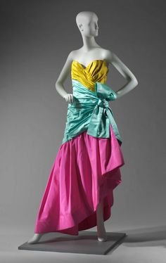 Strapless silk evening gown with yellow bust, turqouise bodice and bow sash, and bright pink asymmetrical hem. Top side zipper with hook and eye clasp. Bust lined with bright pink plain weave silk with boning; skirt with tulle stiffening.