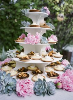 Miniature tarts, displayed on a white tiered pastry tray with succulents and pink flowers.