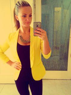 Toda de negro con chaqueta amarilla y collar dorado