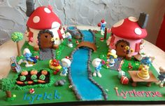 The smurfs' village - Smurfs are plastic figurines provided by client. Everything else is made of fondant. Thanks for looking :)  Www.facebook.com/skyrahrockdesserts
