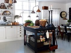 lighting and the island work space... oh and what do you know? there 's the open shelving i adore...