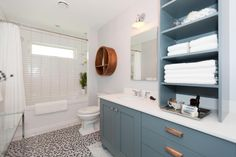 As seen on HGTV's Love It Or List It, Too, Designer Jillian Harris brought order to a disorderly bathroom by consolidating some much needed space. Jillian removed the stand-up shower and replaced it with a double vanity and unified the plumbing to one wall, leaving room for a sleek glass top table. Jillian painted the bathroom Gray Mare and she tiled the bathtub with 2x8 white horizontal subway tile and the floor with a mosaic of grey scale circular tiles.
