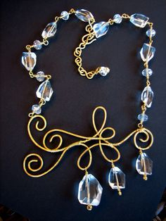 Chandelier crystal statement piece with hand-forged brass scrollwork, and asymmetrical design. This one will turn heads!