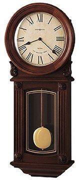 The 625-290 Isabel Quartz Wall Clock by Howard Miller has a pair of carved shell overlays, wood bezel, brass-finished pendulum, and a Windsor Cherry finish.