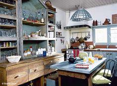 Esprit brocante pour cette jolie cuisine qui mixe parfaitement les matériaux : vaisselier en bois vintage, table de ferme recouverte de zinc et lustre en inox. Une cuisine qui a tout bon ! (Elle Maison)