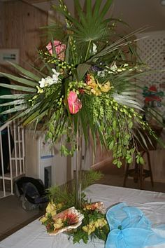 A tall centerpiece from an island wedding, featuring tropical leaves, anthuriums, and dendrobium orchids.  Cymbidium orchids, greens, and shells grace the bottom of the arrangement.