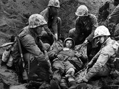 A wounded Marine is transported to an armored vehicle on February 23, 1945 on Iwo Jima.