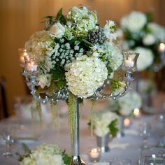 Tall, branch-like candelabras were topped with white hydrangeas, roses and various greens like hanging amaranthus.