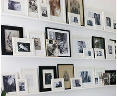 In de woonkamer, naast de inbouwkast, de familie foto's bjj elkaar plaatsen op maat gemaakte smalle, witte plankjes in witte, bruine en zilveren lijstjes.