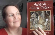 Carma Spence, The Genre Traveler, holding a copy of Swedish Fairy Tales John Bauer, Tv Reviews, Book Review, Science Fiction, Fairy Tales, Horror, Fantasy, Books, Sci Fi