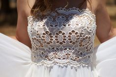 A bohemian bodice made from eyelet lace. This bride was smart enough to wear a flesh tone lining beneath her bodice. Otherwise, we'd see more than the lace.