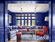 In a Connecticut home designed by Mark Cunningham, an RH sectional sofa anchors the media room, whose walls are coated in Fine Paints of Europe's WC-86 blue. Among the room's red accent pieces are a 1950s Pierre Guariche armchair, a '30s André Sornay stool, and a vintage leather floor lamp by Jacques Adnet.