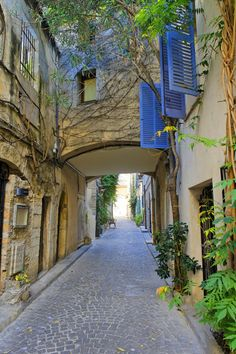 Blue shutters over cobbled stone streets in Antibes, France.