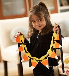 Candy corn garland from paper plates and some paint or colored paper.  Is it just me, or do the black ribbons look like bats?