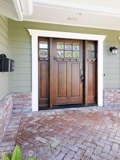 This wooden front door with glass panes is complimented by white trim.The woodwork and trimwork provide nice contrast to brick paver entryway and green/sage siding.  Three-part doors (main entryway with panels) are a great replacement for french doors or a large entry door flanked by glass panels.  Wood stain.