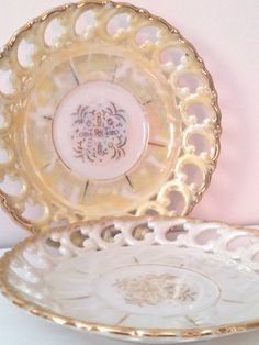 et of two Royal Sealy China tea saucers or small plates. Both saucers have the same pattern with gold trim. They both have an iridescent finish know as Lusterware. Lusterware became popular in Staffordshire during the 19th century.