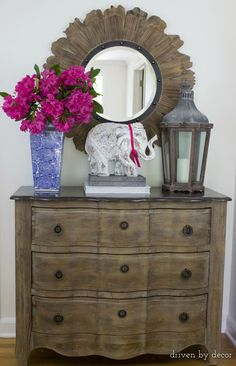 Foyer chest simply styled with flowers in a blue & white vase, a lantern, and a carved elephant :)