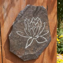 A blossoming lotus is etched into hand-cut pieces of volcanic slate, adding inspiration and beauty to any setting.  Buddhist and yoga wall art is approx. 10 x 12 x 1.