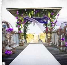 Becky and Mike got married near the ocean underneath a beautiful gazebo decorated with sheer fabrics in lavender and purple, branches, vines, flowers, and sea urchin shells. Fabric ties and urchin shells adorned each row of chairs along the aisle.