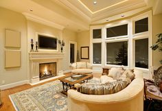 Lovely living room featuring a large patterned rug, beige fireplace, and large bay windows.