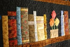 """So clever! """"Bookcase"""" quilt, with different fabric for each book, and tie labels for the titles.  Make It... a Wonderful Life: August's Quilt Group"""