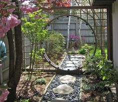 A moongate set in a trellis provides the separation between a dining terrace and small garden beyond.