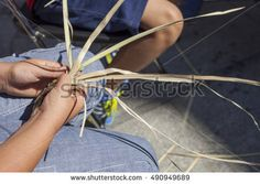 Children learning to plait vegetable fibers. Closeup