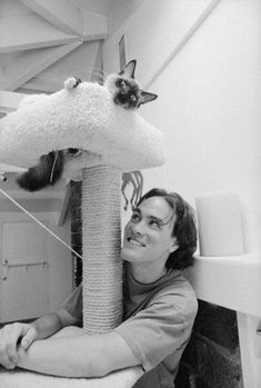 Brandon Lee, star of 'The Crow' (1994), playing with his cat.
