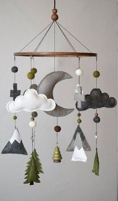 Mountain and Woodland themed nurseries are all the crave right now! I really wanted to capture the minimalist beauty of nature found in the Swiss Alps. You will find white and gray mountains with green accented trees, felt balls and beads as well! The center of the mobile features a large