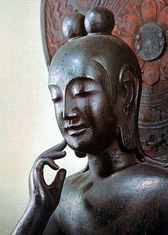 【奈良・中宮寺/菩薩半跏像(飛鳥)】双髷を結い、左足は踏み蓮華の上に載せる。丸みを帯びた体躯は女性的。瞳は彫られておらず、上瞼の下にできる影によって伏目がちに見せる。口元の両端はぼかされ、頬に自然につながるような表現技法をとる。
