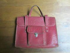 Leren schooltas, een zgn.beugeltas, genoemd naar de metalen beugel (hier aan de achterkant van de tas) waar het rode leren handvat doorheen gehaald moest worden om de tas te sluiten