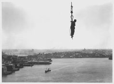A construction worker hangs from a crane cable during construction of the Sydney Harbour Bridge c.1930 - Imgur