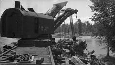: NP Wreckers 41 an 44 with a lift on NP 1356 that is out of the river. NP 1356 derailed after bridge washed out due to high water. Some of wrecker crew are watching blocking to see that blocks don?t slip.  Date: July 10, 1943       Location: Bass, MT       Photographer: Ron V. Nixon  Railroad: Northern Pacific Railway       Station: Bass --- USA