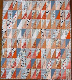 """The finished quilt dimensions: 42″ x 48″  Half Rectangle Triangle Units: 3"""" x 6""""  Batting: Warm and Company Low Loft  Featured Fabrics: So many!  Art Gallery Squared Elements in Mandarin, various Denyse Schmidt prints, Cotton + Steel Bow Ties  Backing and Binding: Riley Blake Vintage Happy"""