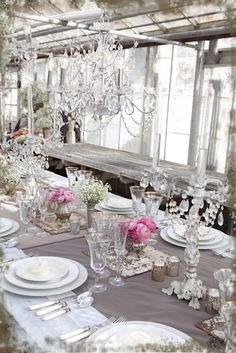 taupe runner on white cloth, pink roses in merc. glass, crystal candlesticks with drop crystals, silver rimmed white plates