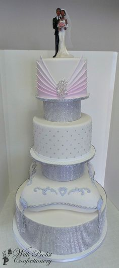 Elegant three tier white and pastel colored wedding cake