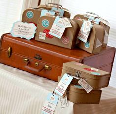 """The favor table, or """"Baggage Claim,"""" was stacked with suitcase gift boxes. Each box had stamps and travel stickers on the outside and was filled with stork cookies created by Becky Melton. The boxes were stacked on top of an old leather suitcase found in a consignment store."""