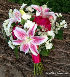 A loosely constructed, round, hot pink, white, and green bridal bouquet featuring stargazer lilies