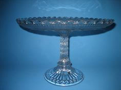 "Glass Cake Stand. Not greek key, but a key design of some other kind. The under side is beaded to look like frosted glass as well as the stem. The stem has a wonderful scale design. 10.5""Dx 7""H. Pattern?? Maker??"