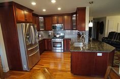Cherry cabinets with a cherry stain. Lighter wood floors, granite counters with a serving peninsula, and stainless steel backsplash.