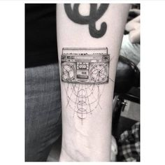 Fine line style boom box tattoo on the left inner forearm.
