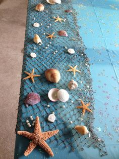 Mermaid Baby Shower. Bag of shells, starfish, pearls and netting from Hobby Lobby & blue table cloth.
