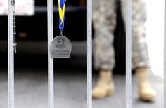 A Rosary, left, hangs from a barricade near a Boston Marathon finishers medal, center,guarded by a Massachusetts National Guard member near a makeshift memorial on Boylston Streetnear the site where a day earlier explosions killed at least three and injured more than 140 in Boston, Tuesday, April 16, 2013. (AP Photo/Julio Cortez)