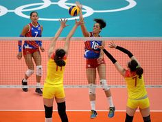 Alexandra Oquendo of Puerto Rico spikes the ball over the block Yunli Xu of China block during a volleyball match between at Maracanazinho in the Rio 2016 Summer Olympic Games.
