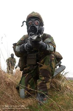 Soldier wearing full Individual Protective Equipment (IPE) is pictured aiming his SA80 rifle during a chemical defence exercise at the Defence NBC Centre, Winterbourne Gunner.
