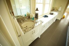His and hers sinks separated by a long storage bench help to preserve the great natural light from a large window while also creating storage and a relaxing atmosphere in a master bathroom. Dark flooring grounds the room while light furnishings preserve a sense of lightness and cleanliness.  #sink #base #white #vanity #stone #counter #bench #bathroom #remodel #master #bath #mirror #cabinet