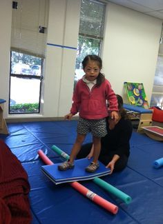 "This ""surfing"" play-based activity requires that a child balance on a boogie board while on pool noodles. This activity not only activates the vestibular system but it also includes gross motor and motor planning skills. Sensory Motor, Gross Motor Activities, Kids Learning Activities, Gross Motor Skills, Sensory Activities, Sensory Kids, Sensory Rooms, Teaching Kids, Dementia Activities"