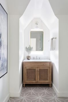 In a cozy nook, a brown washstand fitted with cane doors is accented with a marble countertop and positioned on brown starburst floor tiles under a curved brass mirror hung in front of a window. Bathroom Floor Tiles, Bathroom Renos, Bathroom Interior, Design Bathroom, Bathroom Styling, Remodled Bathrooms, Tile Floor, Transitional Bathroom, Neutral Bathroom