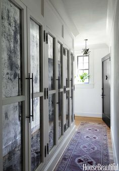 New closets in the entry, with antiqued mirrored doors and French hardware, hold coats and AV equipment.