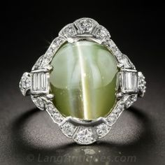 A rare and exotic Art Deco jewel dating from the peak of the period - circa 1925. A mesmerizing chrysoberyl cat's-eye, weighing a sizable 18.50 carats, and imbued with a majestic khaki green hue, winks at you with sharp bright white chatoyancy (i.e. the cat's-eye), from within a stunning mounting hand-fabricated in platinum and sparkling with bright-white European-cut diamonds and on the sides with scrolls of straight baguette diamonds. A unique vintage jewel of surpassing quality. Size 8.